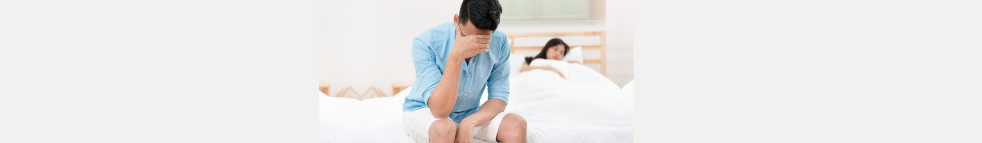 Husband unhappy and disappointed in the erectile dysfunction during sex while his wife sleeping on the bed.