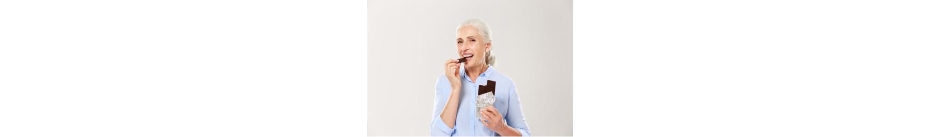 Portrait of cheerful elderly lady eating chocolate